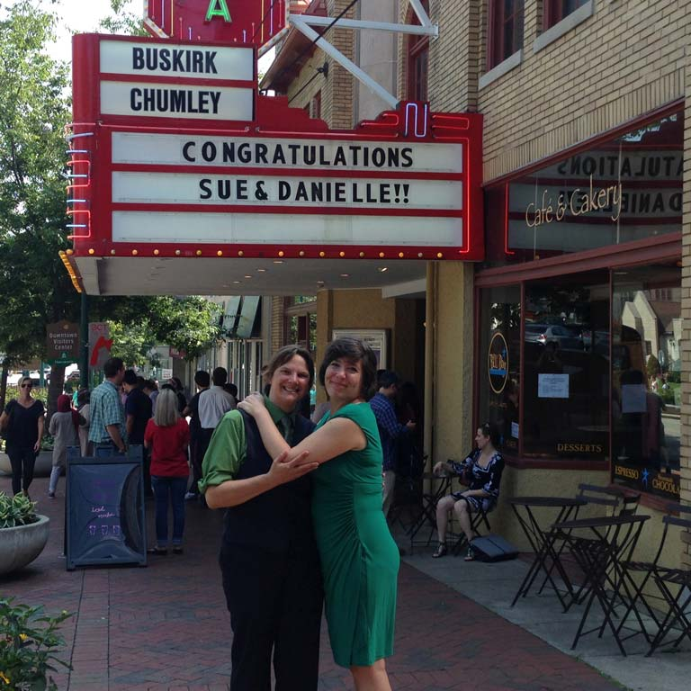 Two women embracing in front of a theatre marquee